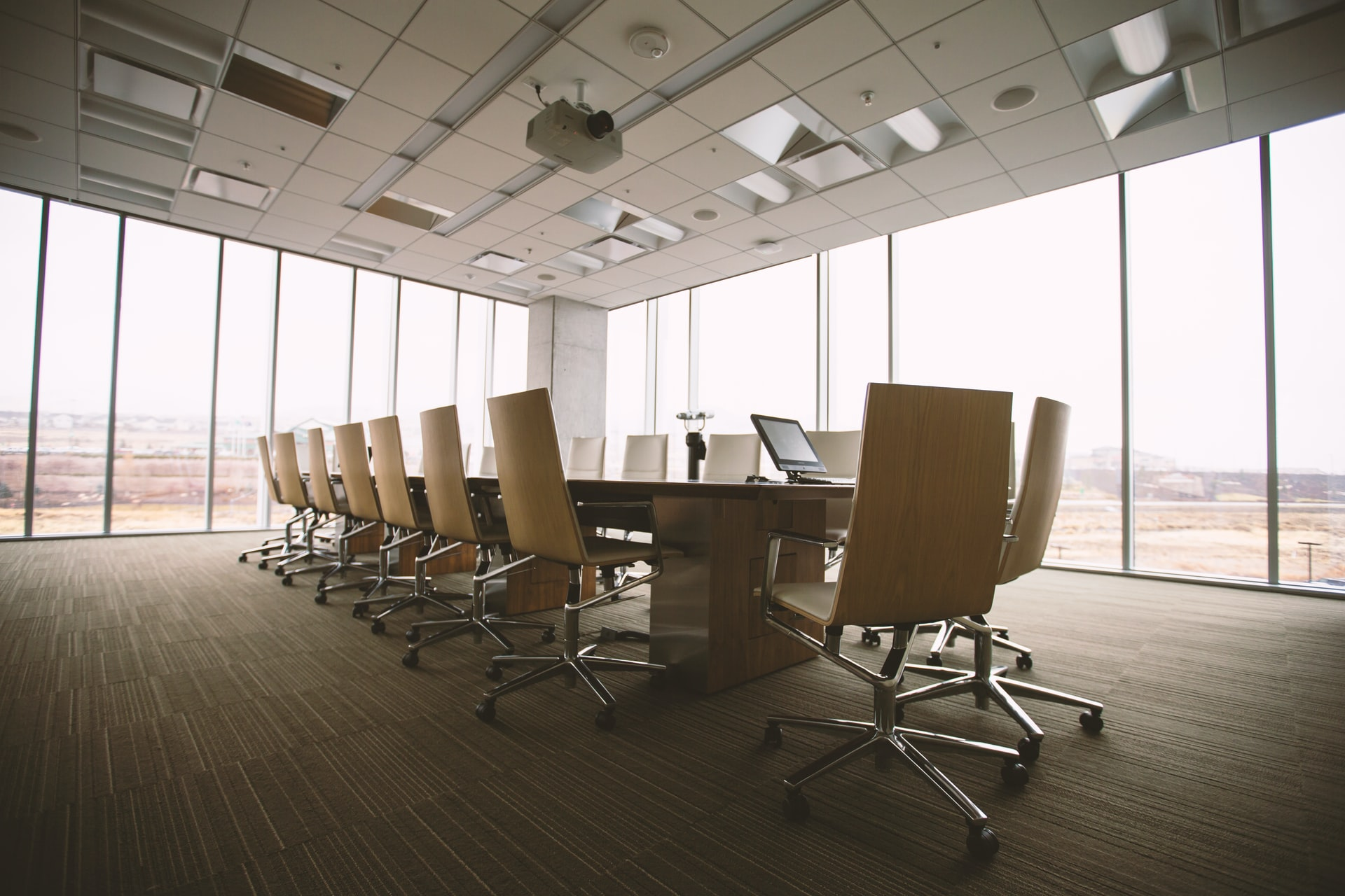 Empty board room with chairs pushed into table and glass walls to the outside